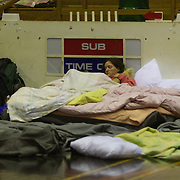 A lady rest next to a basketball scorers bench at the Crowles Stadium in Christchurch used to shelter earthquake victims.  A Powerful earth quake ripped through Christchurch, New Zealand on Tuesday lunch time killing at least 65 people as it brought down buildings, buckled roads and damaged houses, churches and the Cities Cathedral. 23rd February 2011.  Photo Tim Clayton