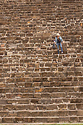 A tourists walks down the steps of the south platform of Monte Albán pre-Columbian archaeological site in the Santa Cruz Xoxocotlán, Oaxaca, Mexico.