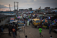 Vendors sell wares in the more established section of the Badia neighborhood of Lagos, Nigeria, September 14, 2013.  Badia, a neighborhood of mostly tin-roofed wooden homes built along a railroad track, is known for its brothels and nightlife.