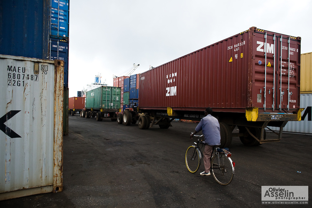 A man rides a bicycle past cargo containers at the sea port in Lome, Togo on Friday October 3, 2008.