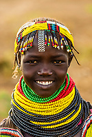 A teenaged Nyangatom tribe girl with many rows of beaded necklaces. They also wear pieces of watch bands as decoration, Omo Valley, Ethiopia.