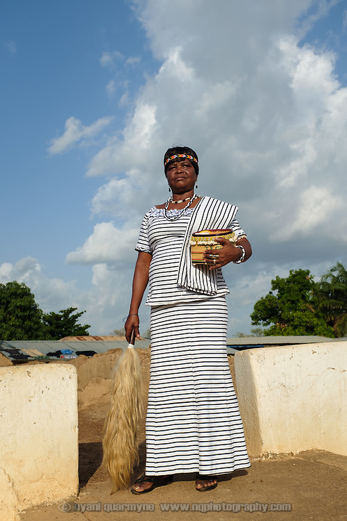 """Pognaa Dogkudome Tegzuylle I of Lyssah within the complex of the Paramount Chief in Lawra in the Upper West Region of Ghana on 28 June 2015. The term """"pognaa"""" is the feminine equivalent of """"naa"""", or chief. A pognaa is responsible, in particular, for the wellbeing of women and children in her area of authority. While the title translates as """"woman chief"""", in practice her authority is  subject to a male chief. The role of the pognamine (plural of pognaa) is being revived after having been suppressed during the colonial era, and they are increasingly seen as a force for development."""
