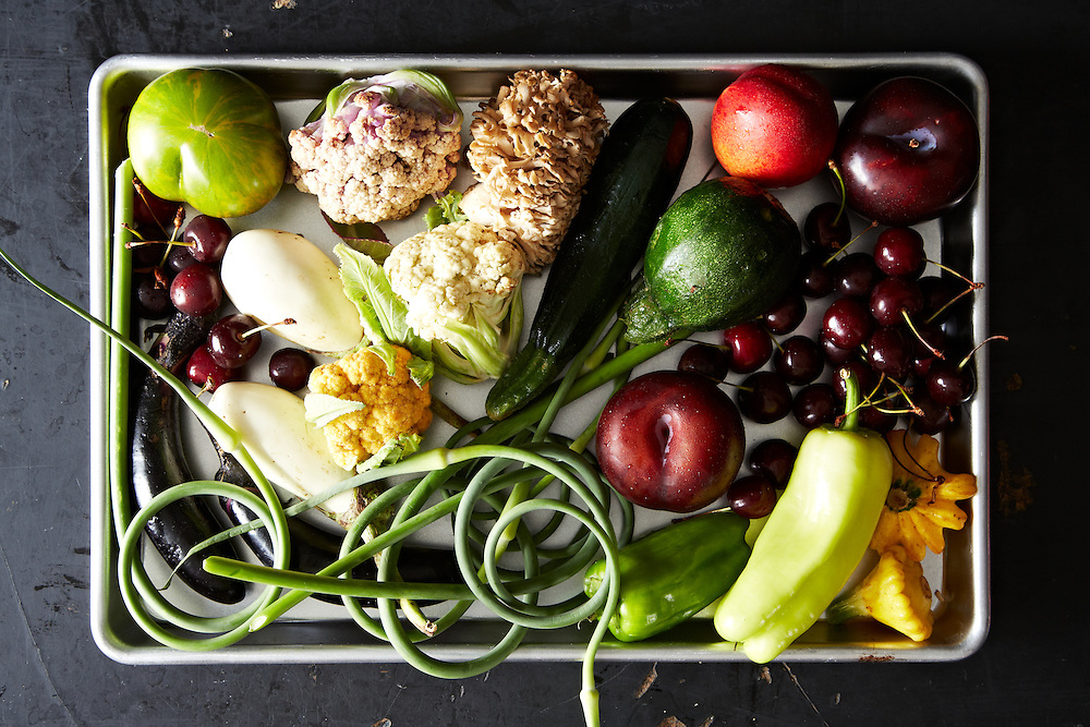 Assortment of raw seasonal fruits and vegetables in a baking tray.