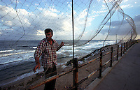 A man sets up a net to try to catch birds for food along the beach in Gaza City. (Photo/Scott Dalton)