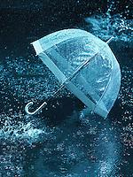 Unused umbrella lying on ground being rained upon