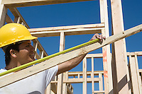 Construction worker measuring plank