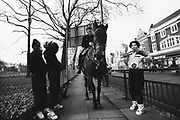 Three young people gurning with a mounted police officer, London, UK, 1980s