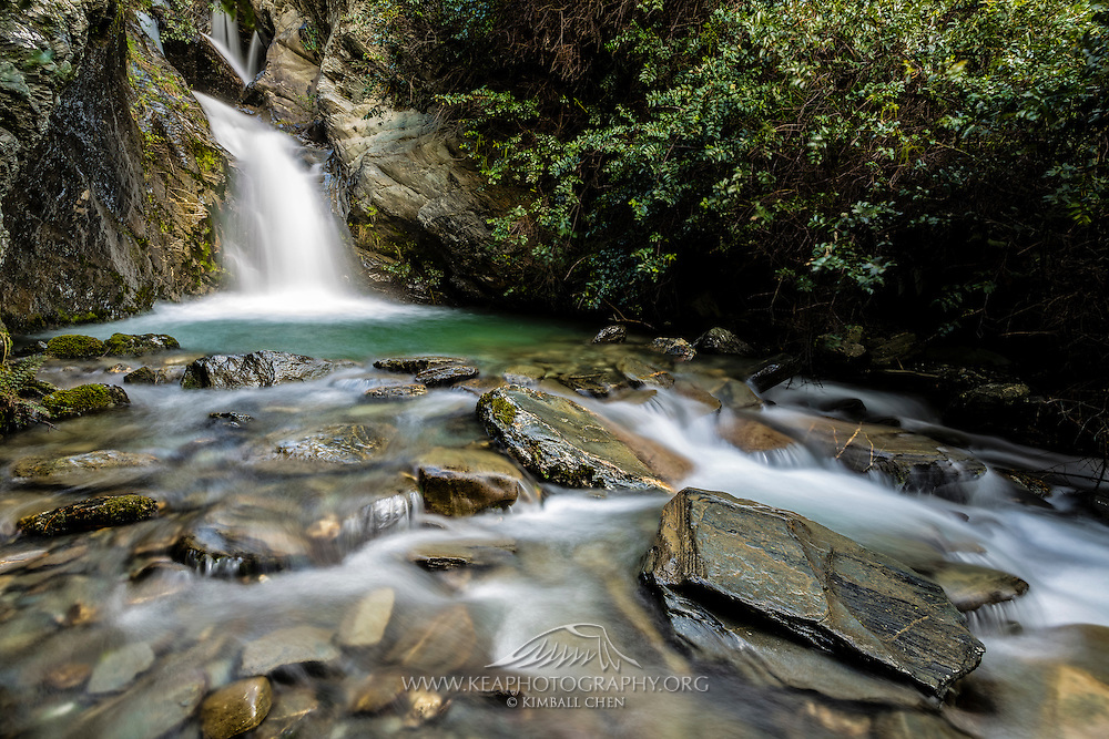 A beautiful cascading waterfall ends in a green pool at Lake Face Creek Falls, along the road from Queenstown to Glenorchy, New Zealand