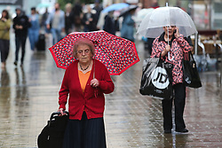 © Licensed to London News Pictures. 22/08/2016. Leeds, UK. Umbrellas are out on a rainy and windy day in Leeds, West Yorkshire. Forecaster are predicting a heatwave this week, but it has started with rain, wind and no sunshine. Photo credit : Ian Hinchliffe/LNP