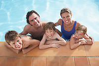 Portrait of family with three children (5-11) in swimming pool smiling