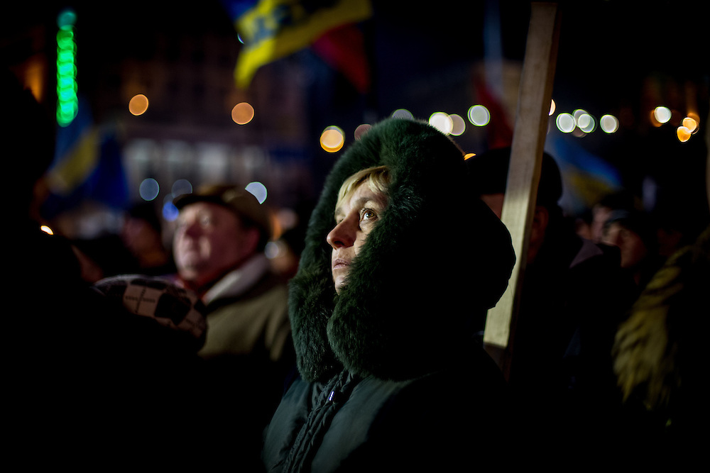 A woman looks at the stage and listens to the speeches, on the Independance Square, at night.
