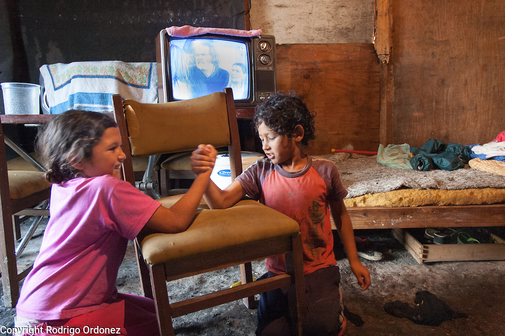 Siblings Jessica, 10 (left), and Pablo, 8, arm-wrestle at their home in Ocho de Mayo. They are part of a family of seven children.