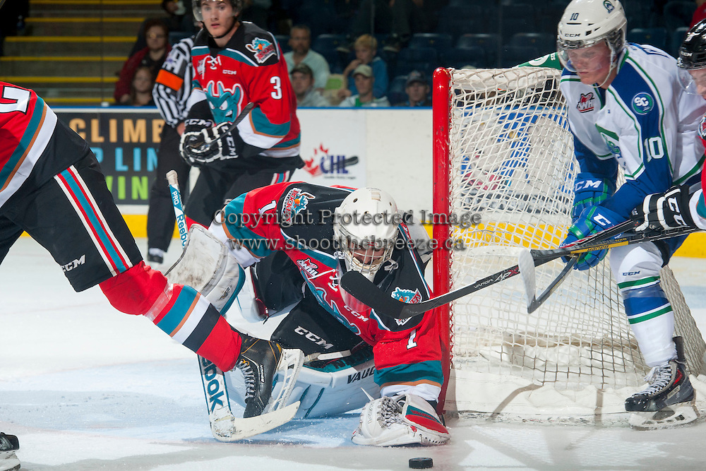 KELOWNA, CANADA - OCTOBER 7: Jackson Whistle #1 of Kelowna Rockets makes a save from a wrap around goal by Colby Cave #10 of Swift Current Broncos on October 7, 2014 at Prospera Place in Kelowna, British Columbia, Canada.  (Photo by Marissa Baecker/Getty Images)  *** Local Caption *** Jackson Whistle; Colby Cave;