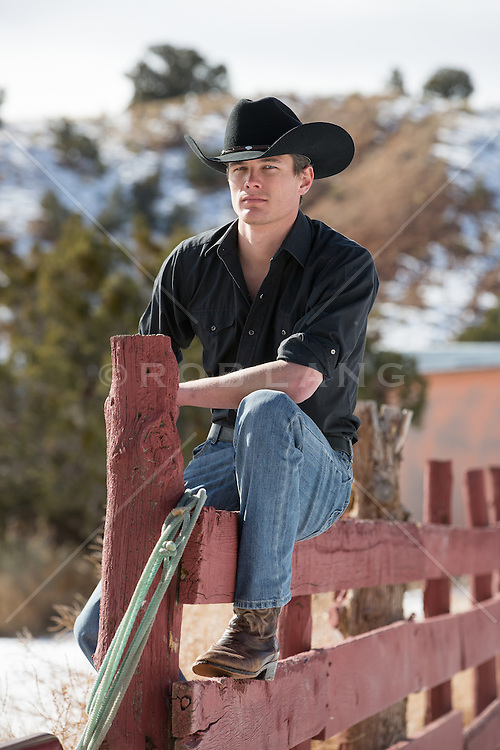 sexy cowboy sitting on a fence on a ranch