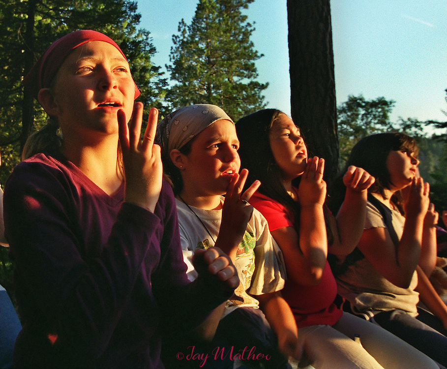 """Girl Scouts, bathed in the lingering glow of sunset, use sign language while they sing a campfire song at Camp Menzies.  The song, """"Moon on the Meadow,"""" reflects upon a time when Native Americans were the original inhabitants of the land whre the camp now exists. The group let ro right: Erin Nash (cq), 10, from San Jose; Kassi Branscom (cq), 10, from Modesto; Alex Norris (cq), 9, from San Jose; Samantha Baxter, 10, from Carmichael.  June 27, 2000.  Sacramento Bee/Jay Mather.The Sacramento Bee"""