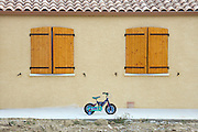 abandoned small children bicycle with training wheels in front of the house