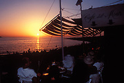 People at a cafe watching the sunset, Ibiza, 1990's.