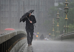 © Licensed to London News Pictures. 29/05/2018. London, UK. A man walks across Westminster Bridge just as thunderstorms bring heavy rain to the capital.  Photo credit: Peter Macdiarmid/LNP