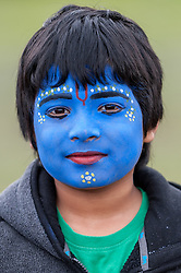 © Licensed to London News Pictures. 05/09/2015. Watford, UK. Idraneel, aged 8, wears blue face-paint with gopi dots during his visit to the biggest Janmashtami festival outside of India at the Bhaktivedanta Manor Hare Krishna Temple in Watford, Hertfordshire.  The event celebrates the birth of Lord Krishna and the festival  includes music, dance, food, dramas and more. Photo credit : Stephen Chung/LNP