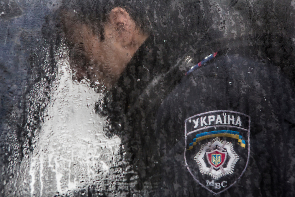 KIEV, UKRAINE - DECEMBER 6: A Ukrainian police officer sits inside a bus during anti-government protests on December 6, 2013 in Kiev, Ukraine. Thousands of people have been protesting against the government since a decision by Ukrainian president Viktor Yanukovych to suspend a trade and partnership agreement with the European Union in favor of incentives from Russia. (Photo by Brendan Hoffman/Getty Images) *** Local Caption ***