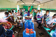 15 JUNE 2013 - YANGON, MYANMAR: A passenger compartment on the Yangon Circular Railway. The Yangon Circular Railway is the local commuter rail network that serves the Yangon metropolitan area. Operated by Myanmar Railways, the 45.9-kilometre (28.5 mi) 39-station loop system connects satellite towns and suburban areas to the city. The railway has about 200 coaches, runs 20 times and sells 100,000 to 150,000 tickets daily. The loop, which takes about three hours to complete, is a popular for tourists to see a cross section of life in Yangon. The trains from 3:45 am to 10:15 pm daily. The cost of a ticket for a distance of 15 miles is ten kyats (~nine US cents), and that for over 15 miles is twenty kyats (~18 US cents). Foreigners pay 1 USD (Kyat not accepted), regardless of the length of the journey.     PHOTO BY JACK KURTZ
