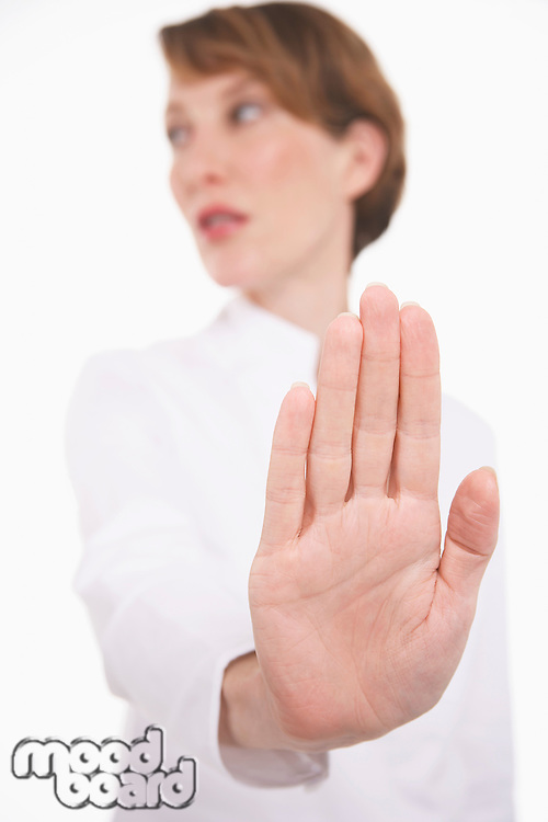 Woman holding up hand studio shot