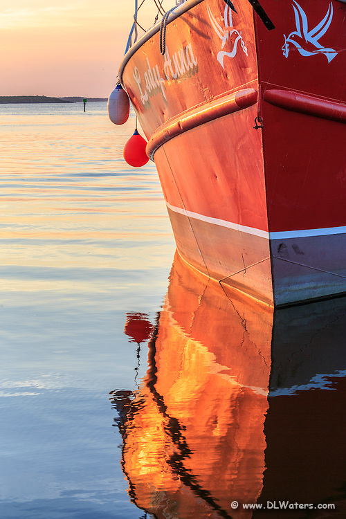 Reflection of the Lady Anna fishing trawler photographed on a calm Wanchese morning.