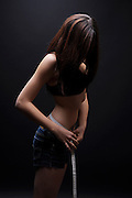 Female teen measures her waist. She may be keeping track of weight loss during a diet but compulsive body analysis may be a symptom of a body image disorder such as anorexia nervosa. Model released