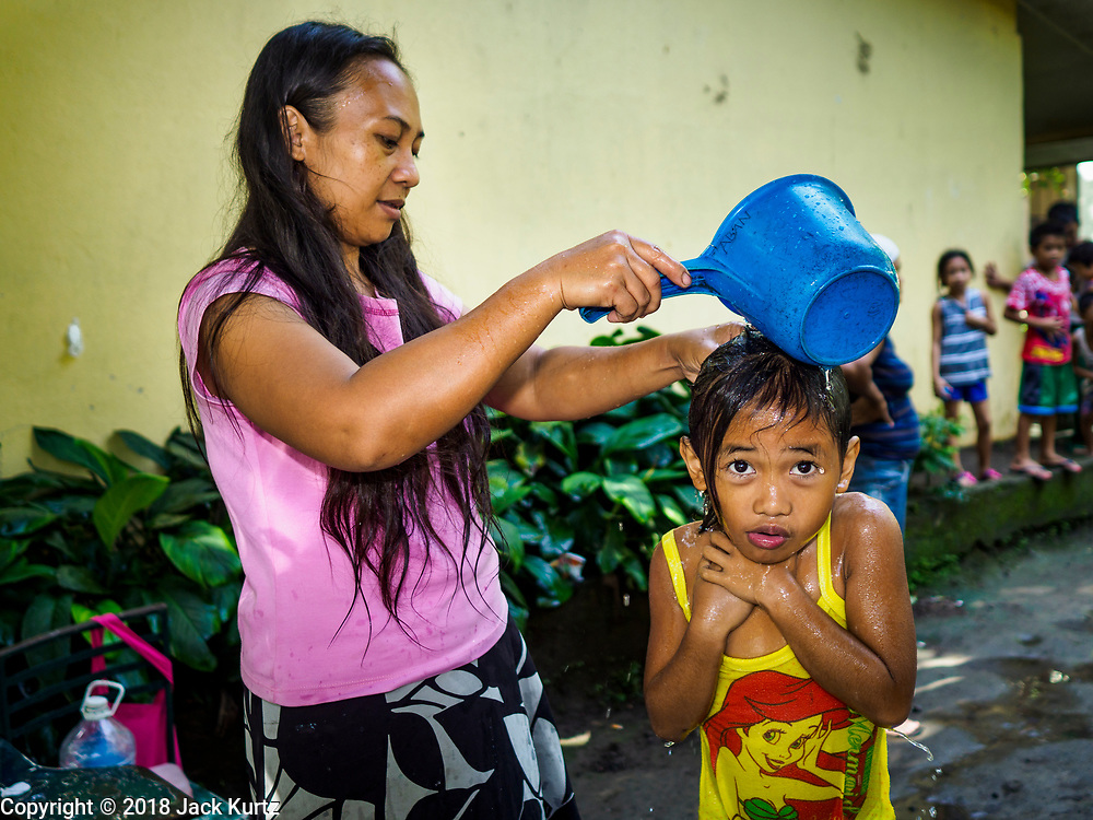 20 JANUARY 2018 - CAMALIG, ALBAY, PHILIPPINES: A woman bathes her daughter at a well in the Barangay Salugan evacuee shelter in a school in Camalig. There are about 870 people living at the shelter. They won't be allowed to move back to their homes until officials determine that Mayon volcano is safe and not likely to erupt. More than 30,000 people have been evacuated from communities on the near the Mayon volcano in Albay province in the Philippines. Most of the evacuees are staying at school in communities outside of the evacuation zone.  PHOTO BY JACK KURTZ