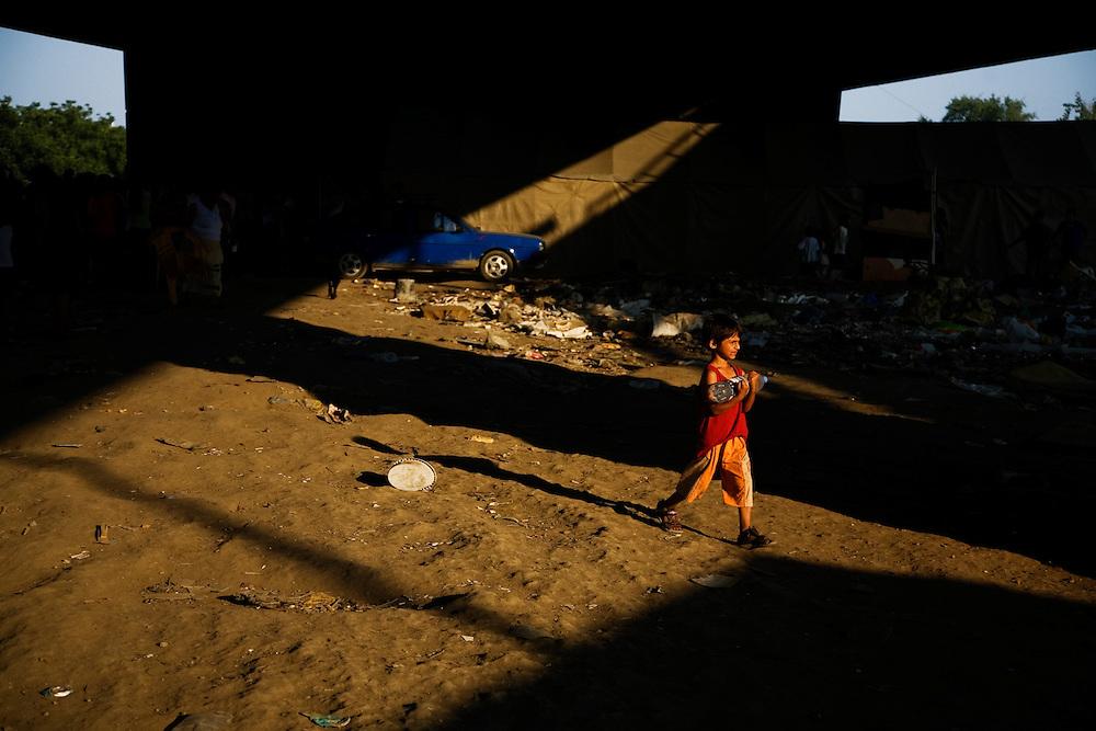 A boy carries a bottle of water to his family under the Gazela bridge in the Nova Gazela settlement.