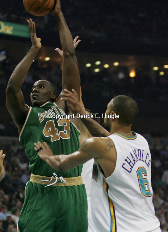 Boston Celtics center Kendrick Perkins shoots between New Orleans Hornets defenders David West (left) and Tyson Chandler (right) in the first quarter of their NBA game on March 22, 2008 at the New Orleans Arena in New Orleans, Louisiana.