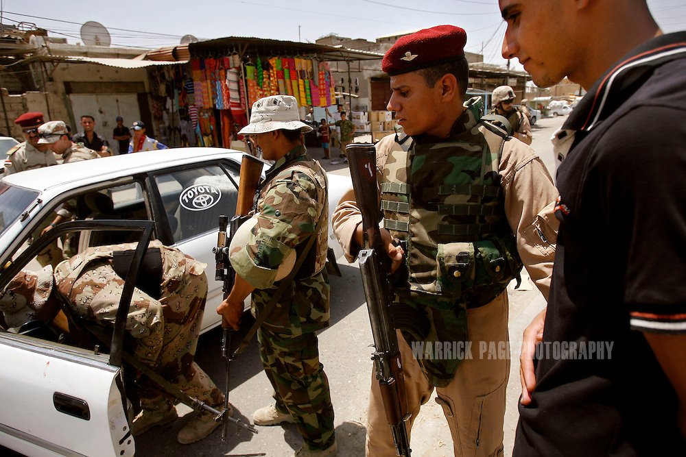 BASRA, IRAQ - JULY 5: Iraqi soldiers stop a young man driving erratically through a crowded marketplace during a joint patrol a with US Marines in the poverty stricken neighborhood of Hayaniyah, July 5, 2008, Basra, Iraq. When British forces withdrew in 2007, Basra deteriorated into street battles between numerous Shiite militias and criminal gangs. In April 2008, Iraqi prime minister, Nouri al Maliki, sent two Iraqi army divisions to retake control of Basra. While the fighting has ended, unemployment is rife, at about 70 per cent. Since early 2008, Iraq's security situation has improved with oil production increasing, record government surplus and easing sectarian tensions. (Photo by Warrick Page)