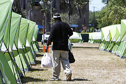 April 2, 2020, Tampa, Florida, USA: A resident walks to his tent with bags of personal belongings and supplies. After two days the emergency homeless shelter set up by Catholic Charities of the Diocese of St. Petersburg and the City of Tampa was completely filled. 'Hillsborough Hope' will provide shelter, food and medical treatment to 100 homeless people through the coronavirus shutdown. (Credit Image: © Luis Santana/Times/Tampa Bay Times via ZUMA Wire)