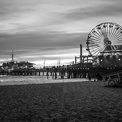 Santa Monica Pier black and white photo at sunset at Santa Monica Beach. Santa Monica Pier is along the Pacific Ocean in Southern California in he United States. Copyright ⓒ 2017 Paul Velgos with All Rights Reserved.