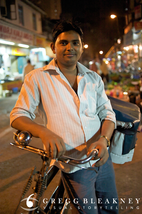 One of Akran's clients, a bread deliveryman, picks up his bike late at night after his taco-ed front rim was repaired. Fort Market - Bombay, India