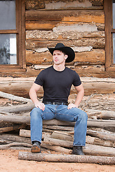 hot cowboy seated by a rustic cabin