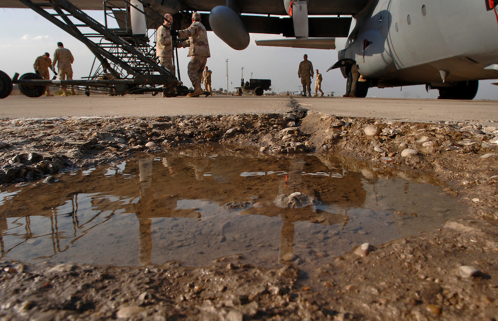 On a flightline pockmarked with morter craters, Iraqi crew chief students work on their C-130E Hercules cargo aircraft. They are performing a propeller 15-day inspection at the 23rd Squadron, New Al Muthana Air Base on Baghdad International Airport, Iraq. (U.S. Air Force photo by Master Sgt. Lance Cheung)<br />