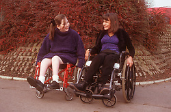 Two teenage girls with disabilities; who are wheelchair users; talking together in playground,