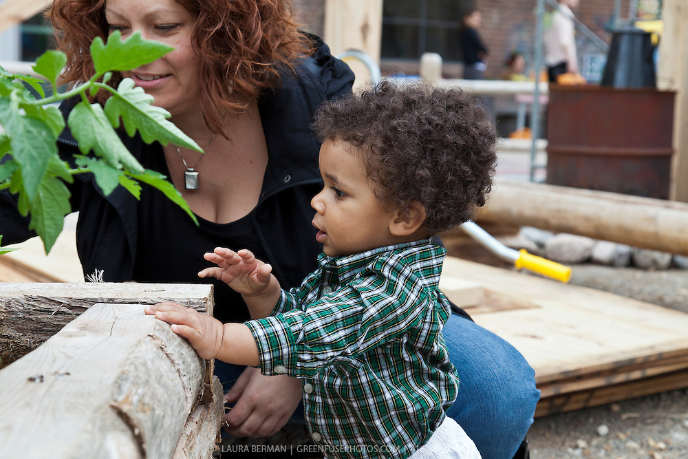 A toddler and his mother investigating nature and edible plants at FoodShare's Pollinators' festival at the Evergreen Brick Works