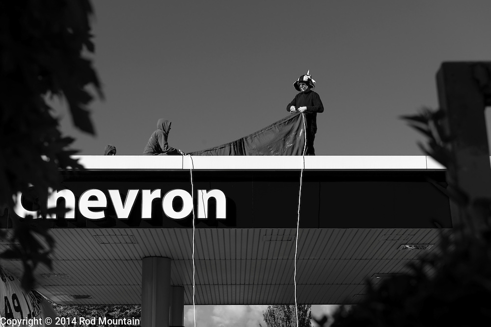 Vancouver, BC, Canada - September 27, 2014 - Young men arrange banners atop a Chevron gas station during the &quot;Party Against the Pipelines&quot; Protest in Vancouver, B.C. <br />