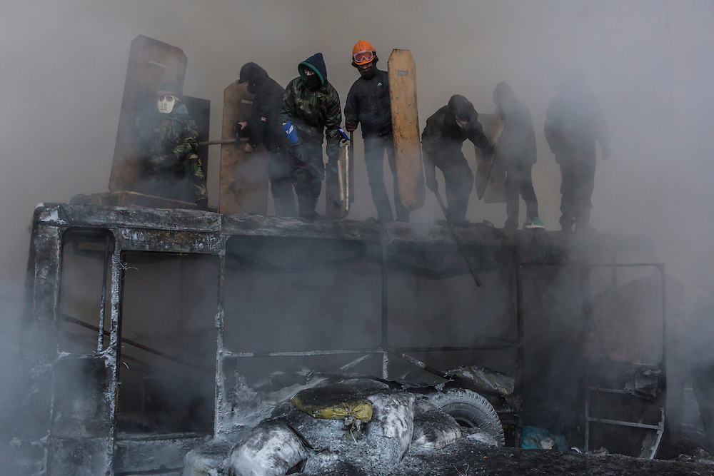 KIEV, UKRAINE - JANUARY 25: Anti-government protesters are engulfed by smoke and steam as police spray water on burning tires during clashes with police on Hrushevskoho Street near Dynamo stadium on January 25, 2014 in Kiev, Ukraine. After two months of primarily peaceful anti-government protests in the city center, new laws meant to end the protest movement have sparked violent clashes in recent days. (Photo by Brendan Hoffman/Getty Images) *** Local Caption ***
