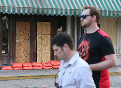 Local residents Ian Campbell, left, and James Quinn pass by a boarded-up, sand-bagged store along River Street on Friday, Sept. 8, 2017, in Savannah, Ga. The city is under mandatory evacuation by Saturday. (Photo by Curtis Compton/Atlanta Journal-Constitution/TNS/Sipa USA)