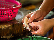 02 SEPTEMBER 2015 - BANGKOK, THAILAND: A vendor cleans squid in the Bang Chak Market. The Bang Chak Market serves the community around Sois 91-97 on Sukhumvit Road in the Bangkok suburbs. About half of the market has been torn down, vendors in the remaining part of the market said they expect to be evicted by the end of the year. The old market, and many of the small working class shophouses and apartments near the market are being being torn down. People who live in the area said condominiums are being built on the land.         PHOTO BY JACK KURTZ