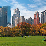People relaxing in Sheep Meadow in Central Park, New York City on a warm autumn day. The Time Warner Center and apartment buildings of Central Park West are in the background.