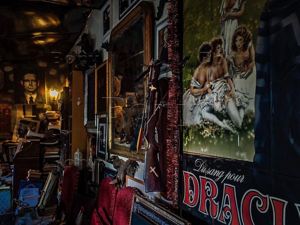 """Arbalète anti-vampire<br /> Paris, avril 2017.<br /> «Nous avons toujours été un pays de légendes, il serait temps de l'assumer.»<br /> Jacques Sirgent, auteur né au Canada de parents français est depuis toujours un passionné des thèmes liés au vampirisme. Il a fondé le musée des vampires et monstres de l'imaginaire à Paris.On dit de lui qu'il est le 1er """"vampirologue"""" au monde.Après un passage un jardin qui se charge de vous mettre dans l'ambiance (graffitis mystiques, pierres tombales, squelettes et totems d'animaux fantastiques accrochés aux arbres, certains le disent hanté) on découvre le musée, composé d'une seule pièce.Ancien atelier de sculpture du père de Jacques Sirgent, l'endroit rassemble des centaines d'objets sur le mythe du vampire.<br /> <br /> Cette collection personnelle donne des frissons : chauve-souris conservée sous verre, rangées de livres anciens sur le Mal, tableaux, poupées, et quelques bizarreries sympathiques comme cette arbalète anti-vampire ou encore cet authentique kit de protection contre les vampires datant du XIXe siècle… Quelques pièces collector, aussi : la machine à écrire de Bram Stoker, le mythique auteur de Dracula, ou des affiches dédicacées de tous les acteurs qui ont interprété le vampire au cinéma.<br /> Le musée possède une bibliothèque dont certains ouvrages remontent au XVIIesiècle et qui se compose de plus de 1500 ouvrages<br /> Si vous êtes émotif, évitez la visite par une nuit sans lune."""