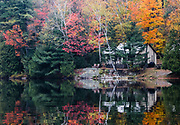 Lakeside reflections of a cottage and fall foliage in Haliburton County, Ontario.