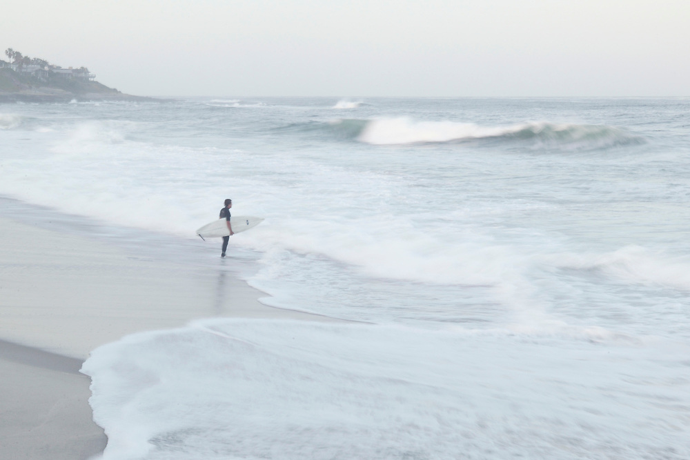 Man alone on beach with surfboard