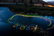 World champion squirt boater, and new Men's mystery move record holder Stephen Wright, who scored a 49 second ride at the world championships recently, works on his mystery moves at night on the Truckee River near Reno, Nevada just prior to the world mystery move championships. This concept shoot using glowsticks attached to the athletes squirtboats is designed to show the underwater trajectory and flow of this unique form of kayaking.