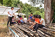 Myo Aung of Shan Youth Power (SYP) helps teach a Saturday class of Shan, English and mathematics to children of Shan migrant workers at Ban Pong Yai Nai, Chiang Mai, Thailand on July 9, 2011. There are about 300 families of ethnic Shan migrant workers from Burma in the area, with about 100 families sending children aged 5-16 years old to the SYP Saturday classes. The children of documented migrant workers study at regular Thai school during the week.