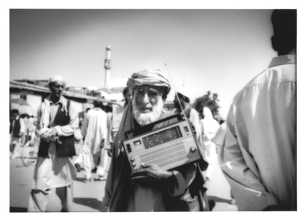 Old Kabuli man carries his transistor radio in an old city market, Afghanistan.